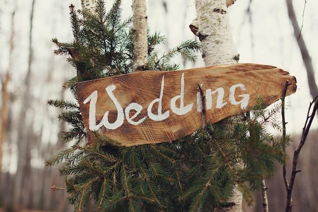 Word 'wedding' written on wooden board hangs on the tree