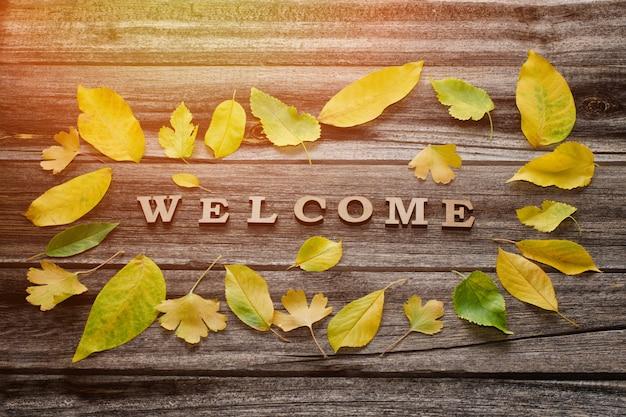 Слово добро пожаловать на деревянном фоне, рамка из желтых листьев