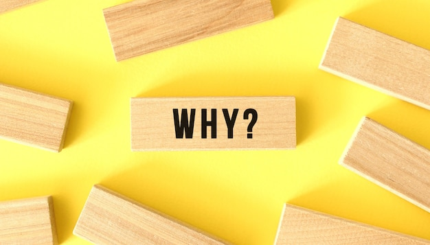 The word why is written on a wooden block with more around on a yellow background
