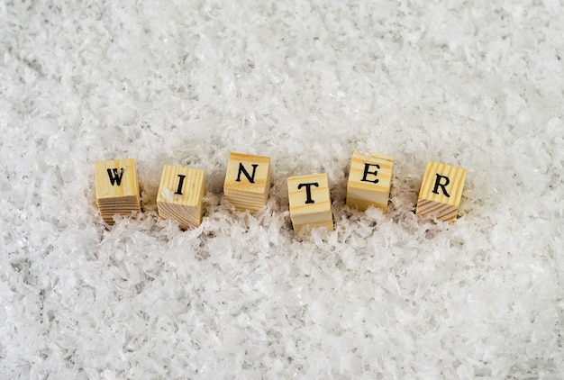 The word winter made of letters on wooden cubes on a snow
