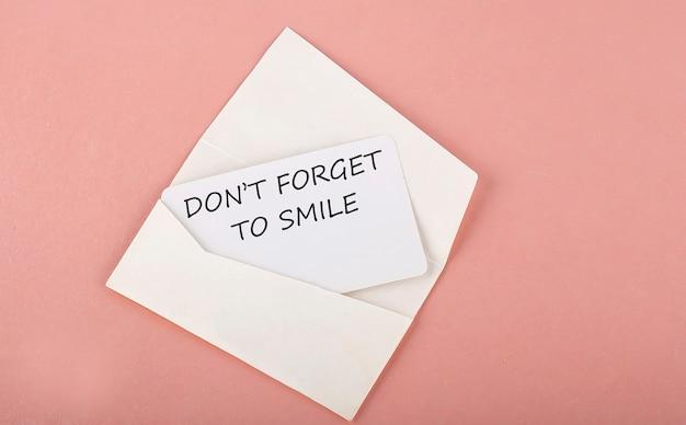 単語の書き込みテキストピンクの背景のカードに笑顔を忘れないでください