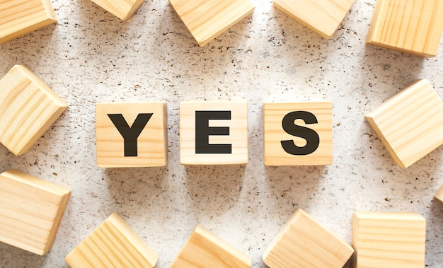 The word yes consists of wooden cubes with letters, top view on a light surface