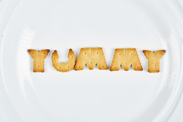 Word yummy spelled with crackers on a white plate.