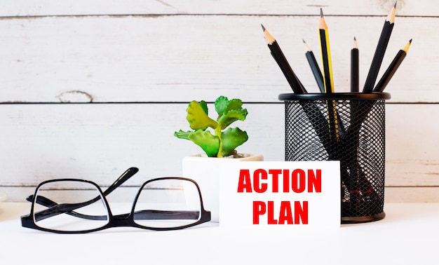The words action plan written on a white business card next to pencils in a stand and glasses