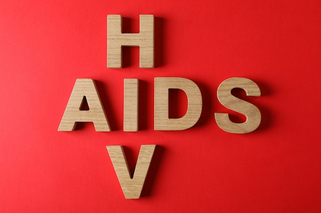 Words aids and hiv on red wall, space for text