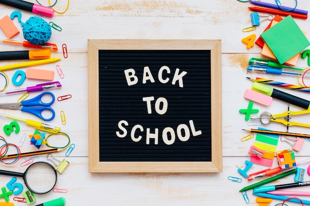 The words back to school written in chalk on school desk with school supplies close-up