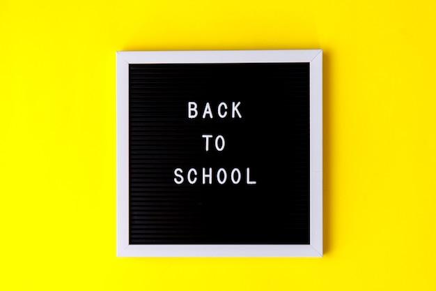 黄色の背景に学校に戻る言葉。教育、学校のコンセプトに戻る、トップビュー、フラットレイアウト