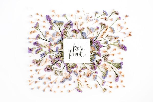 白地に青と紫のドライフラワーを紙に書道で書いた「親切」の言葉。フラットレイ、トップビュー