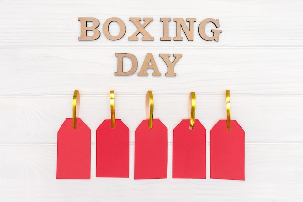 Above words boxing day and five red tags on wood white background