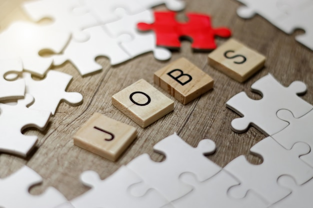 Words of business job in wooden cubes and jigsaw puzzle. business concept.