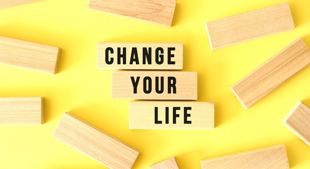The words change your life are written on scattered wooden blocks on a yellow background