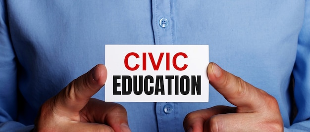 The words civic education is written on a white business card in a man's hands. business concept