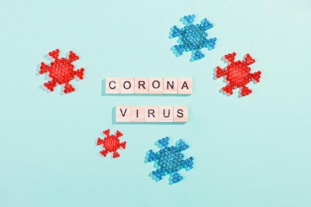 ブルーテーブル、フラットレイアウト、トップビューでコロナウイルスモデルと木製のブロックで作られた単語コロナウイルスの発生。パンデミックのコンセプト