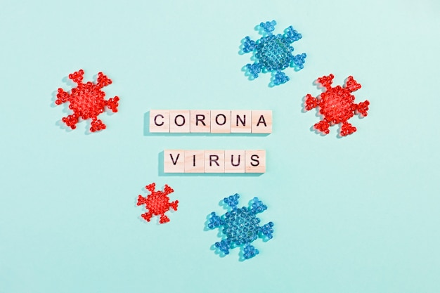 Words corona virus outbreak made of wooden blocks with coronavirus model on bluetable, flat lay, top view. pandemic concept
