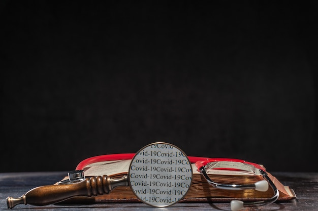 The words of covid 19 are readable through a magnifying glass. stethoscope lying on the medical book. the concept of humankind's knowledge of coronavirus.