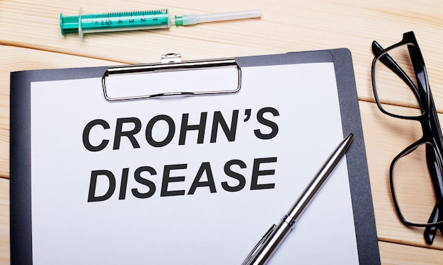 The words crohn is disease is written on a white piece of paper next to black-rimmed glasses, a pen and a syringe