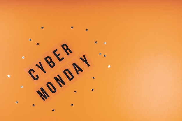 The words cyber monday on a bright orange sequined background. flat lay, copy space
