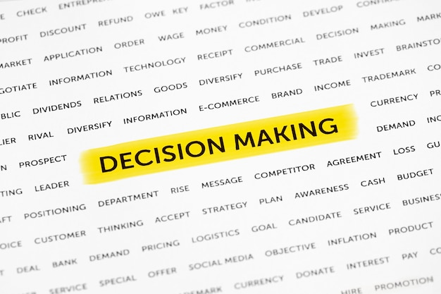 The words decision making is highlighted with a marker on paper
