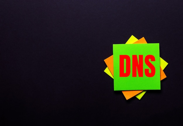 The words dns domain name system on a bright sticker on a dark surface. copy space