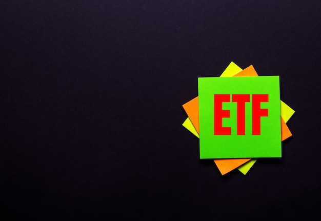 The words etf exchange traded funds on a bright sticker on a dark surface. copy space.