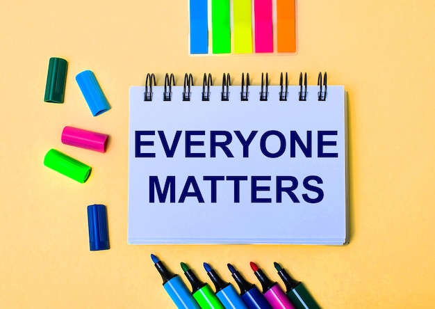 The words everyone matters written in a white notebook on a beige background near multi-colored markers