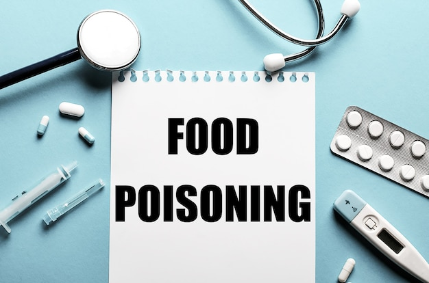 The words food poisoning written on a white notepad on a blue background near a stethoscope, syringe, electronic thermometer