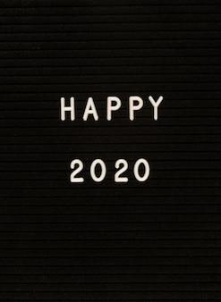 Words happy 2020 on black felt letter board