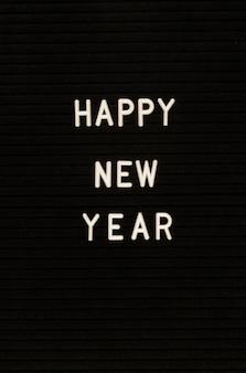 Words happy new year on black felt letter board