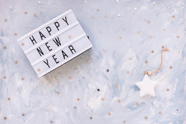 Слова с новым годом с украшением конфетти серебряные звезды на синем фоне. подготовка к новому году