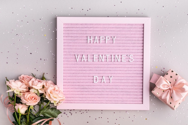 Words happy valentine's day on pink felt letter board. festive composition with a bouquet of roses and a box with a gift on a gray table. top view, flat lay. copy space.