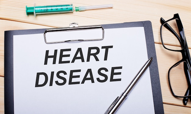 The words heart disease is written on a white piece of paper next to black-rimmed glasses, a pen and a syringe