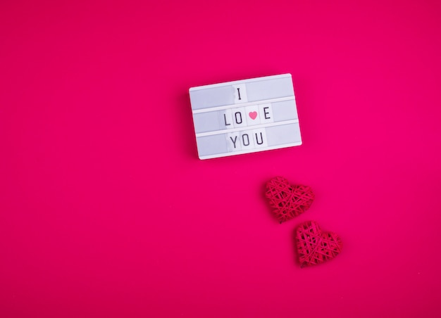 Words i love you on the light box on a pink background with hearts.
