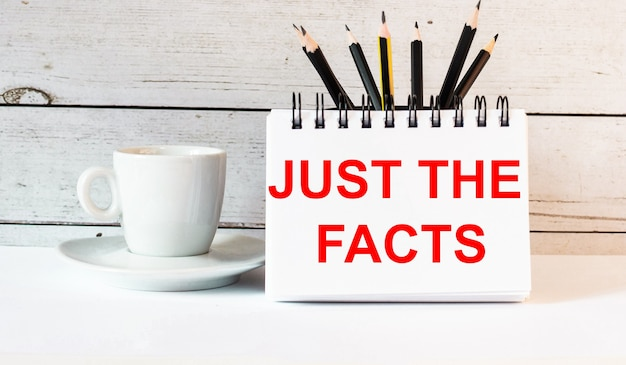 The words just the facts is written in a white notepad near a white cup of coffee on a light surface