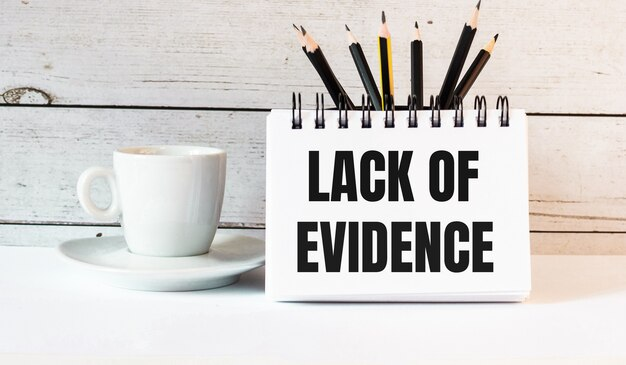 The words lack of evidence is written in a white notepad near a white cup of coffee on a light background