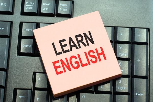 単語は、黒いキーボードの背景に付箋紙に書かれた英語を学びます。英語を学ぶことを示す概念的なテキストキャプションのインスピレーション。