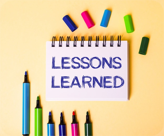 The words lessons learned written in a white notebook on a beige background near multi-colored markers