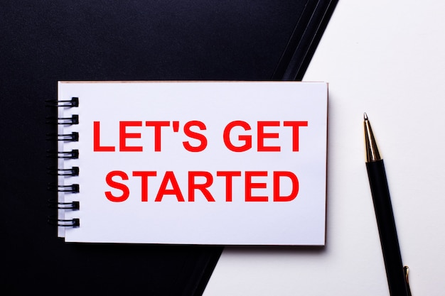 The words let is get started written in red on a black and white background near the pen