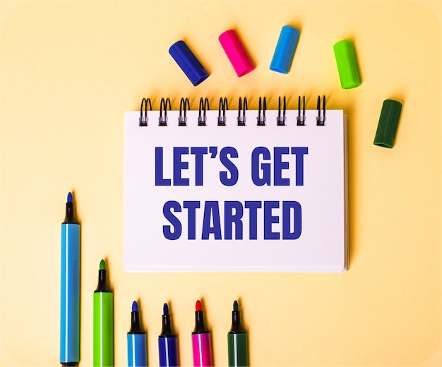 The words let is get started written in a white notebook on a beige background near multi-colored markers