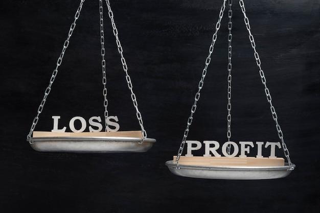 Слова потеря и прибыль в балансе. весы на черном фоне
