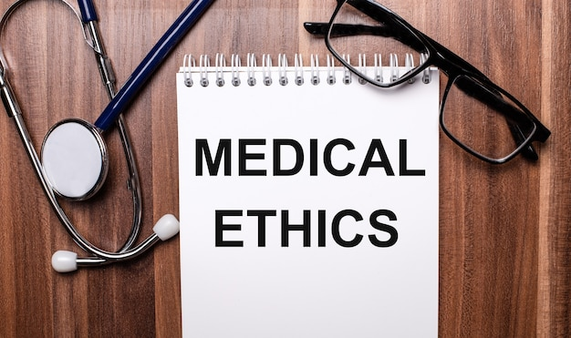 The words medical ethics is written on white paper on a wooden background near a stethoscope and black-framed glasses. medical concept