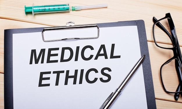The words medical ethics is written on a white piece of paper next to black-rimmed glasses