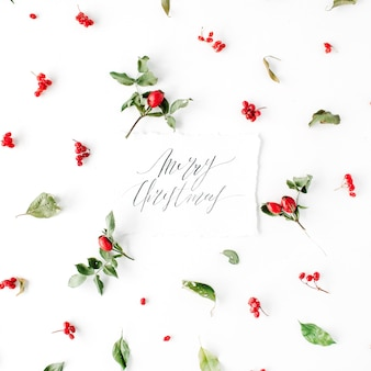 Слова счастливого рождества и минимальный творческий узор расположения ягод на белом.