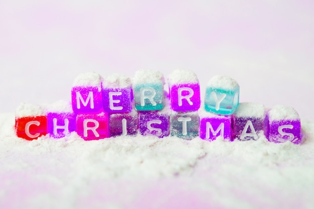 Words merry christmas made of colorful letters blocks on white snow background