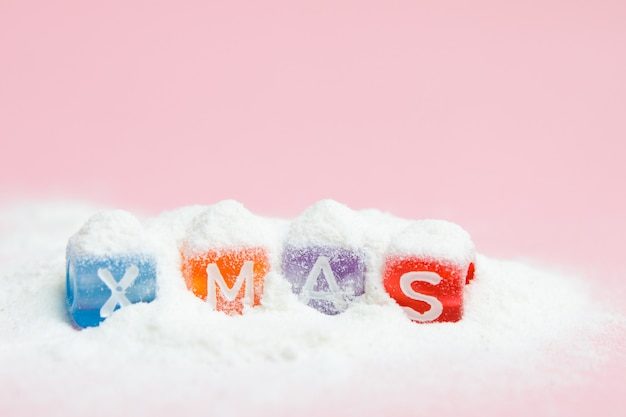 Words merry christmas made of colorful letters blocks on white snow and pink