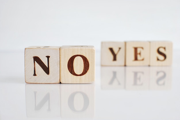 Words no and yes on wooden blocks.