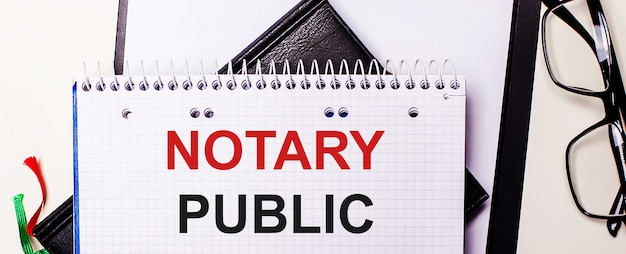 The words notary public is written in red in a white notebook next to black-framed glasses