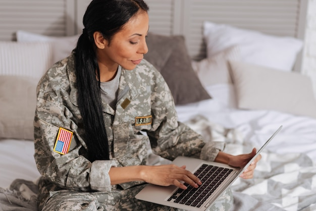 사랑의 말. 침대에 앉아 주말 동안 휴식을 취하는 동안 노트북을 사용하여 친구에게 편지를 쓰는 영리한 감정적 인 매력적인 여성