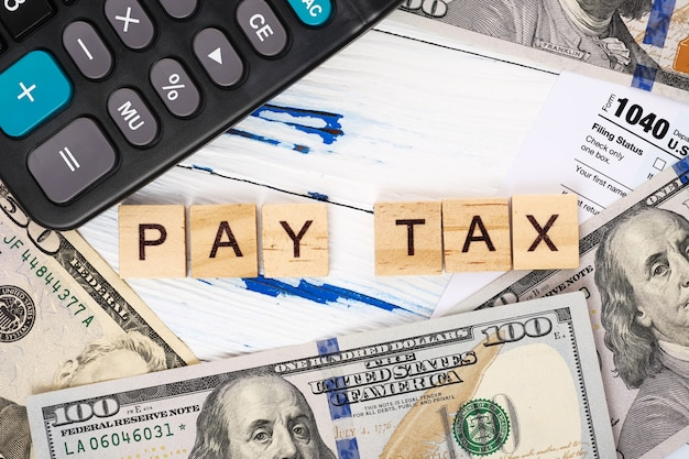 Words pay tax on form 1040, dollar bills and calculator.