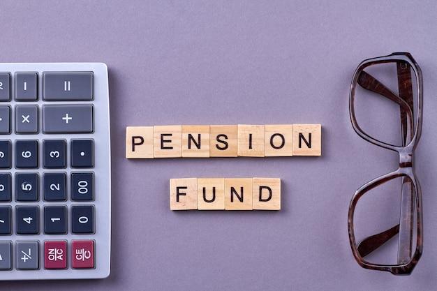 Пенсионный фонд слов с калькулятором и очками на столе.