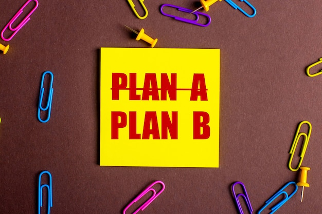 The words plan b is written in red on a yellow sticker on a brown surface next to multicolored paper clips